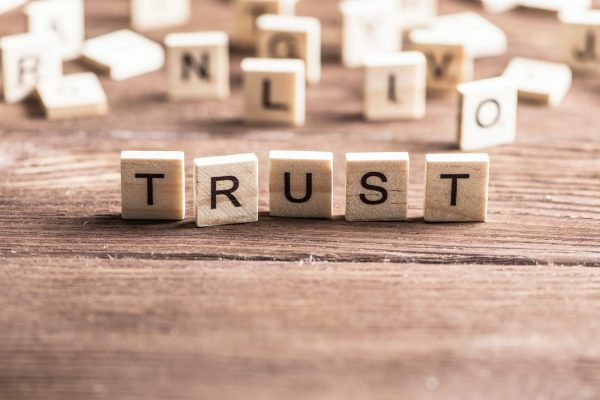 The word Trust is spelt out using small wooden tiles