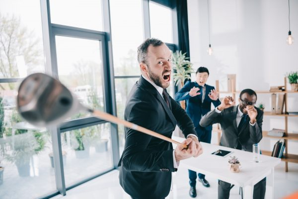 Angry manager swinging a golf club whilst other workers look scared