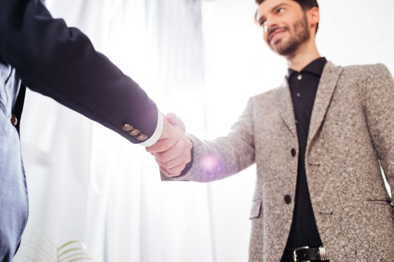Close up photo of men business handshake in office, respectful, integrity