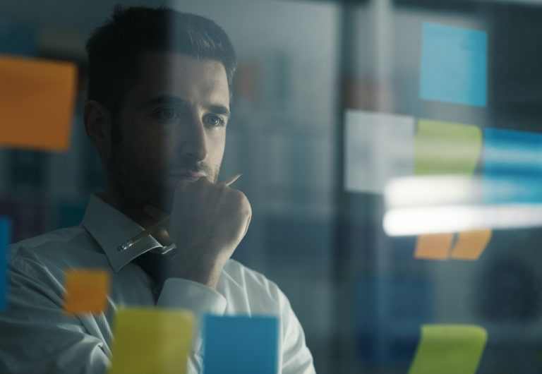 Businessman looking at sticky notes on a wall and looking thoughtful