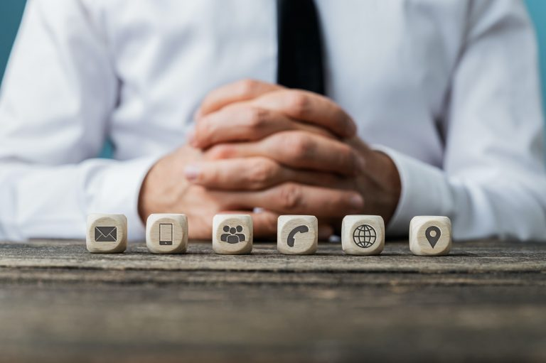 Six wooden cubes with different icons on sat in front of businessman
