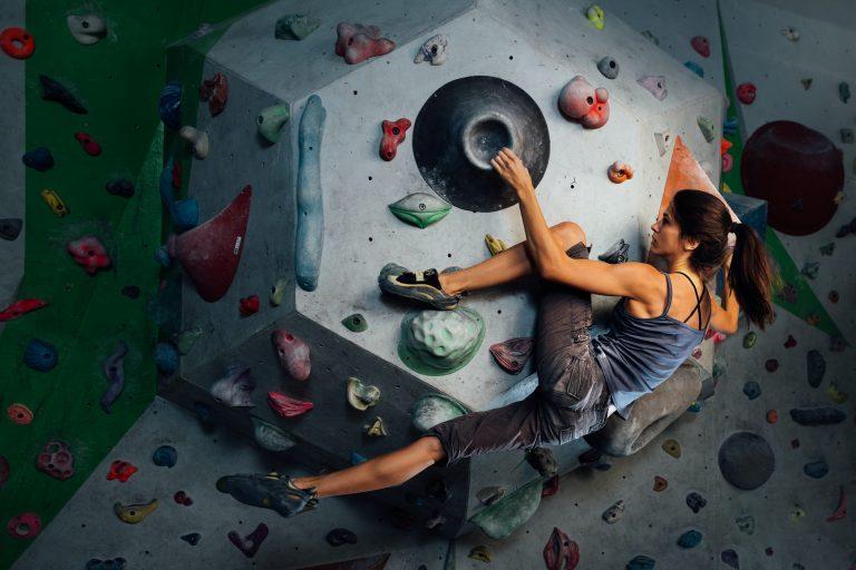Woman in gym wear climbing a climbing wall
