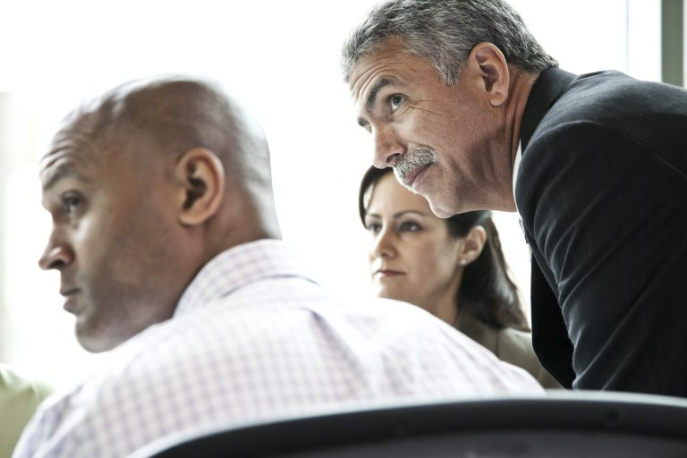 A businessman listens to a conversation in a business meeting