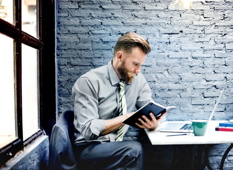 Businessman at desk looking at a notebook with laptop in front of him
