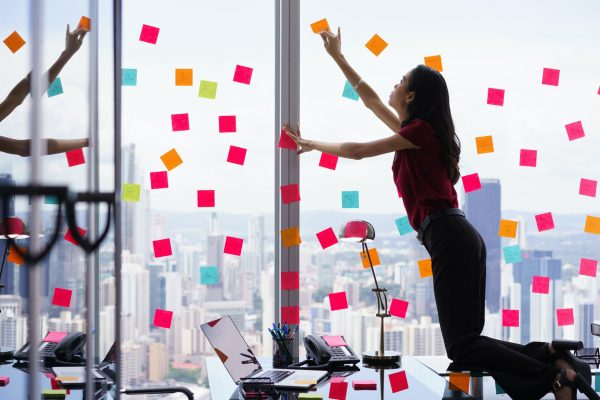 Woman standing on desk, attaching sticky notes to window