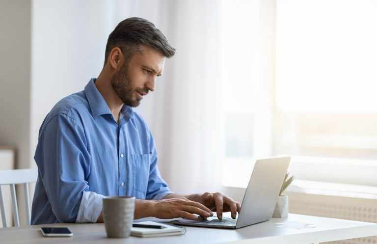 Freelancer Working On Laptop At Desk In Home Office