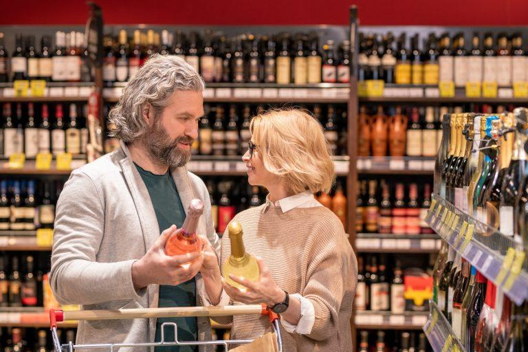 Couple choosing wine while standing among shelves