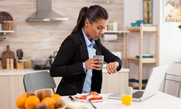 Woman in kitchen staring alarmingly at her watch because she's late