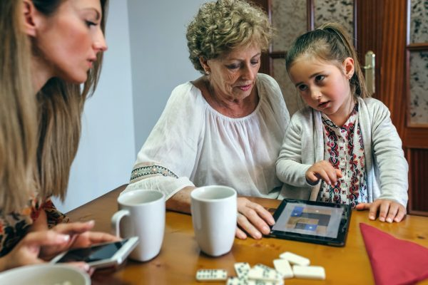 Little girl sat with adults and playing on tablet
