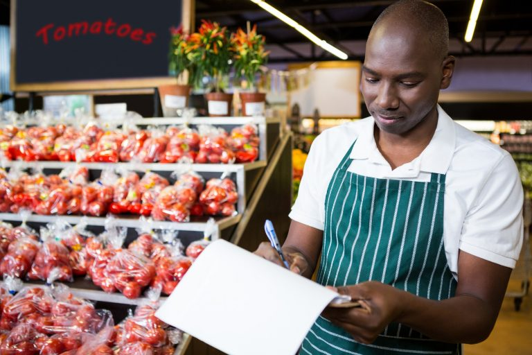 Male staff writing on clipboard in super market