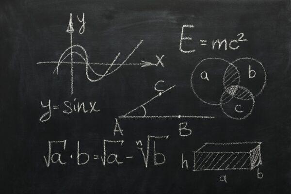 Math formulas on black chalkboard, business equations
