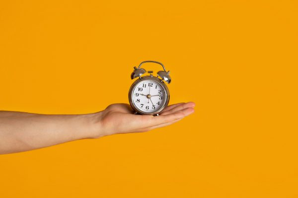 A hand holding an alarm clock on an orange background