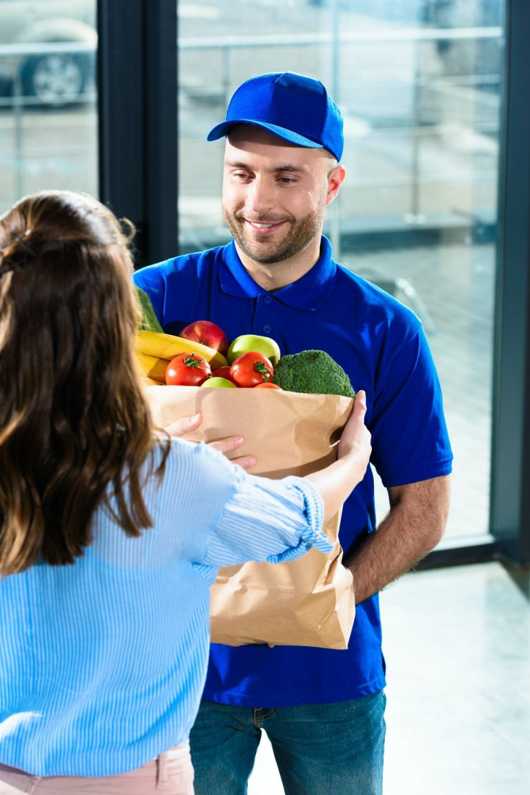 Woman receiving groceries in bag from courier dressed in matching hat and t-shirt