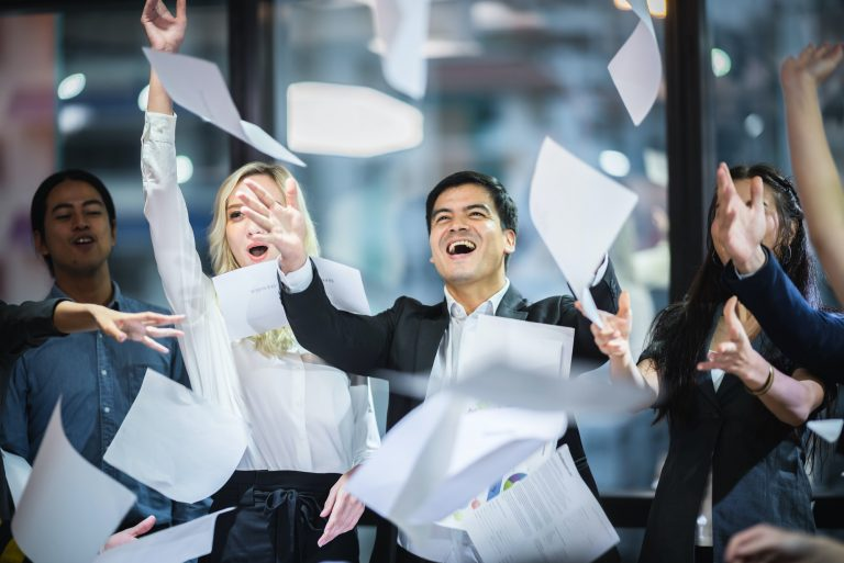 A group of business people are throwing papers into the air in celebration