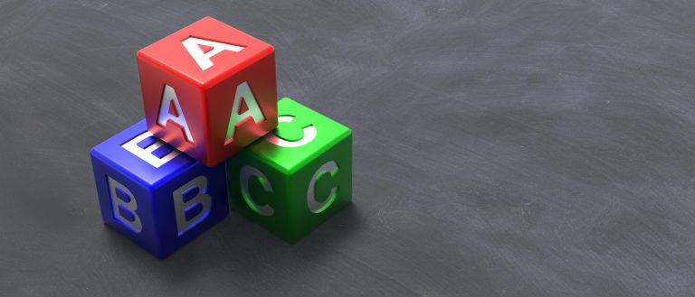3 coloured blocks with A B and C written on laid on a black surface