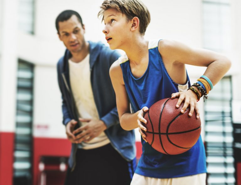 Young boy playing basketball with his coach mentoring him