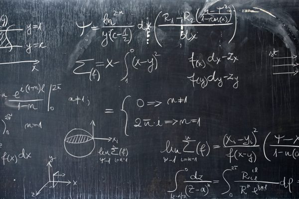 A black board with mathematical equations written across in white chalk