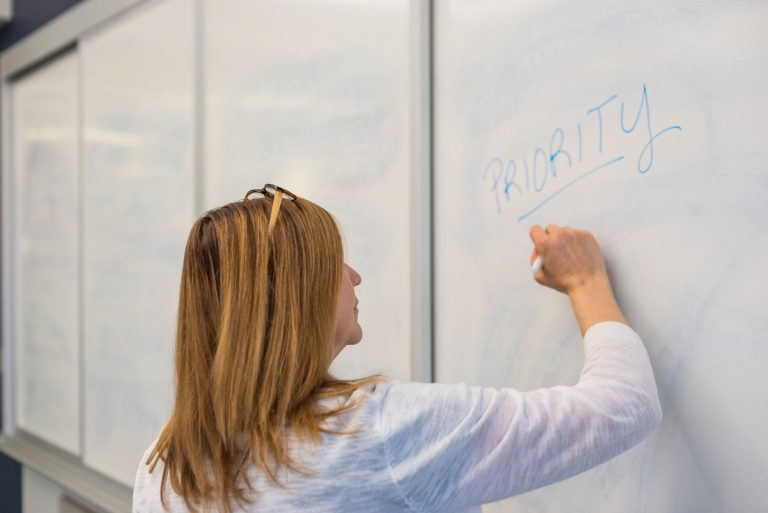 Businesswoman writing the word Priority on a whiteboard