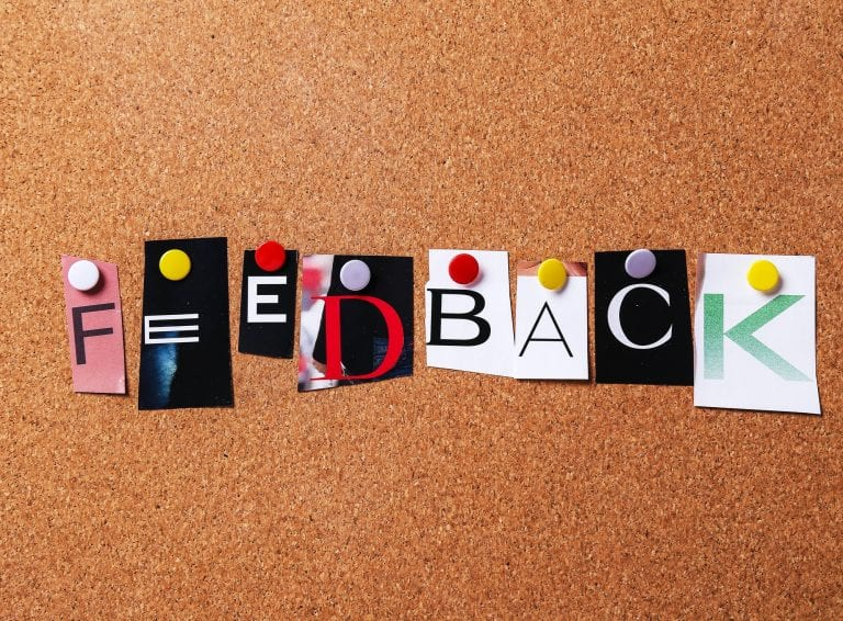 The word feedback cut out of a magazine and pinned to a cork board