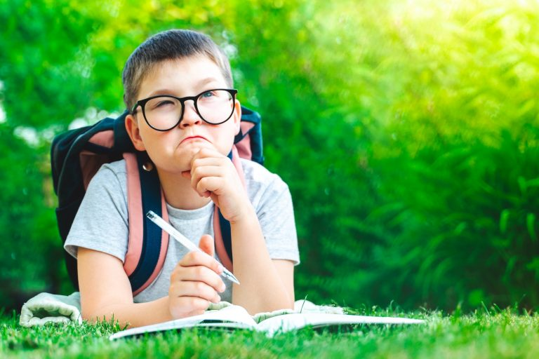 Young boy laying on grass with backpack on school yard doing homework