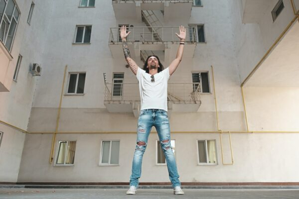 Man standing in front of a building white hands up