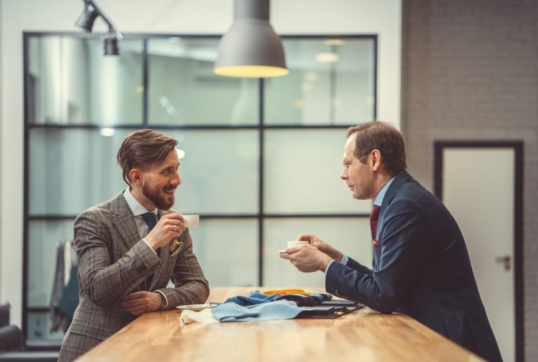 Two businessmen sat having a conversation over coffee