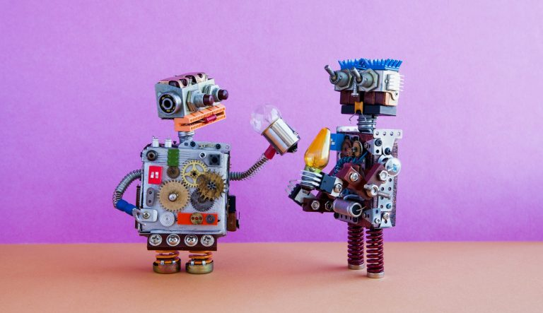Two small robots in conversation, holding lightbulbs