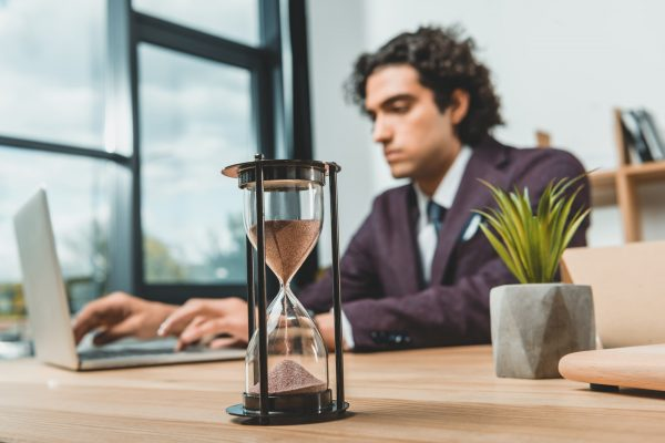 Sand timer on desk with focused businessman in background