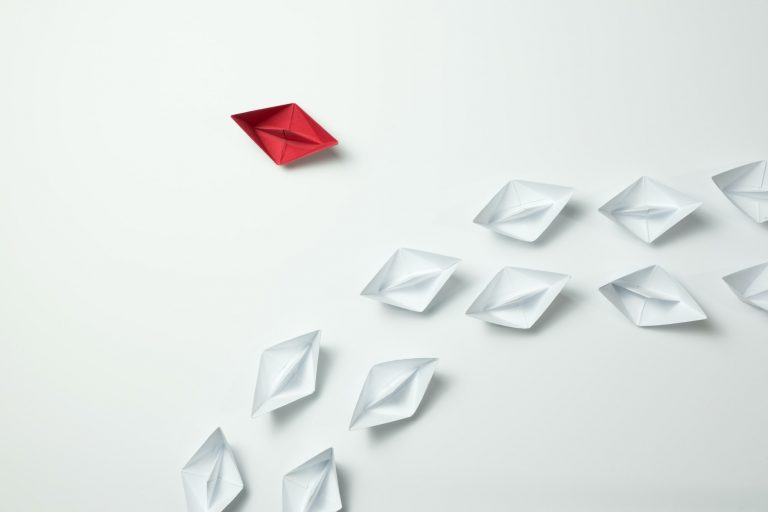 A row of origami white boats following a single red boat