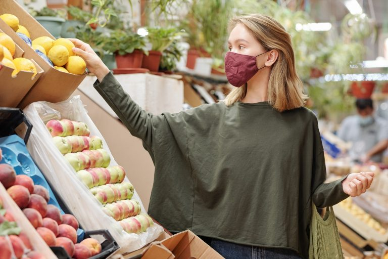 Woman shopping for groceries with face mask on during covid-19