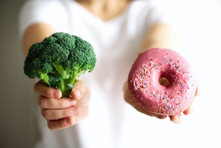Choosing between broccoli or junk food, donut. Healthy clean detox