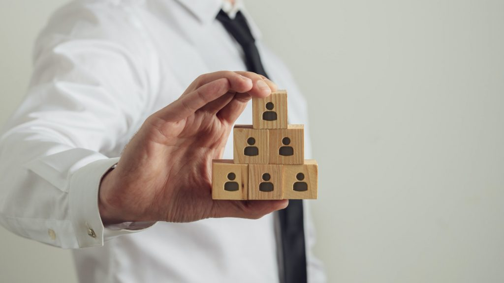 Man holding wooden block with figures on
