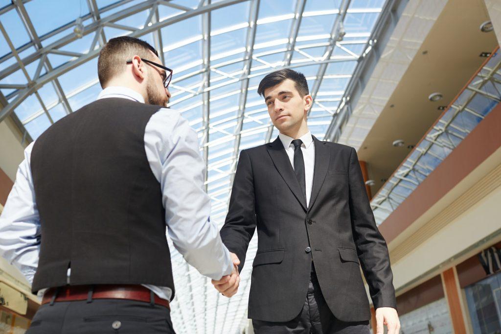 2 businessmen shaking hands outside