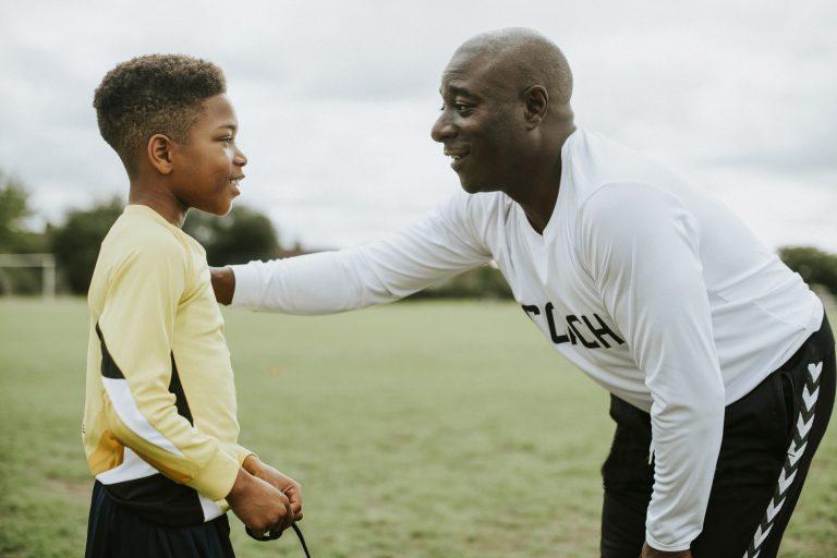 Football coach advising young boy