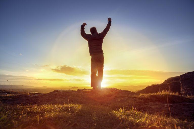 Happy man celebrating winning success against sunset
