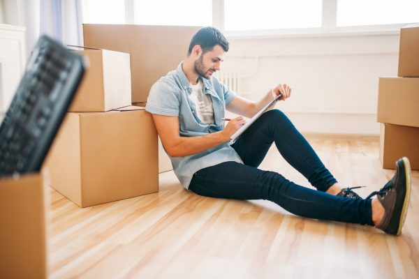Man sat on floor surrounded by cardboard boxed