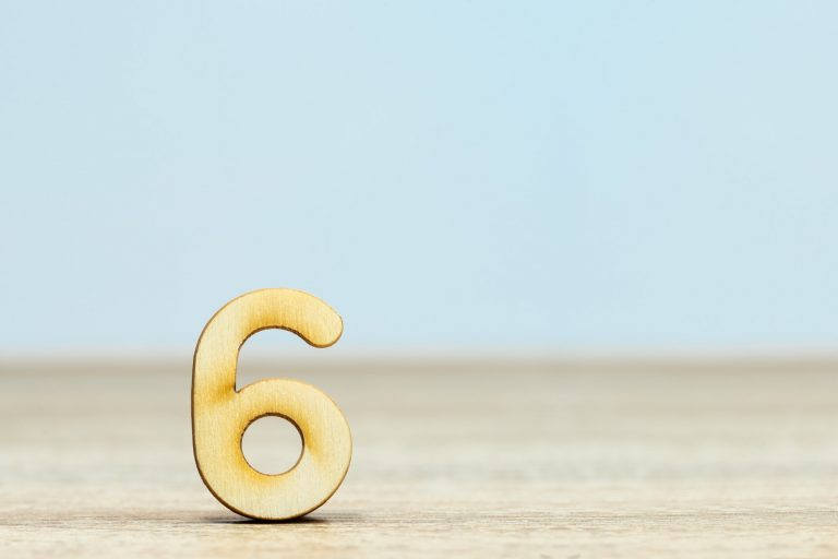 Gold number six on wooden surface
