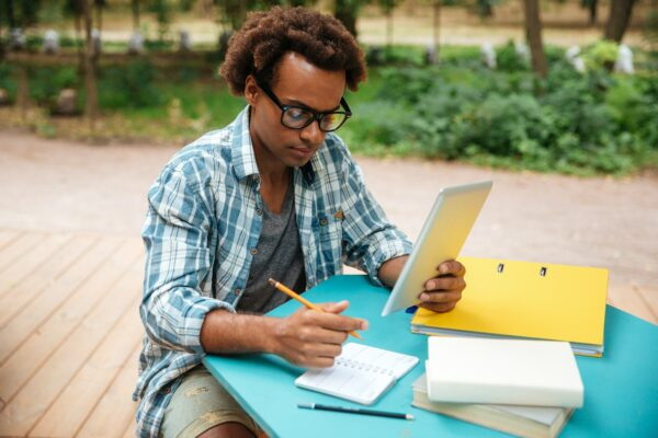 Man learning on outside table