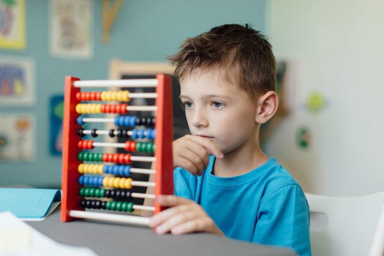 Thinking schoolboy with an abacus