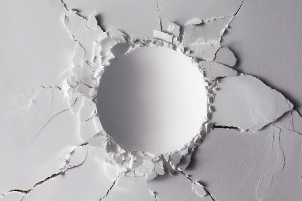 Impact hole in a white wall