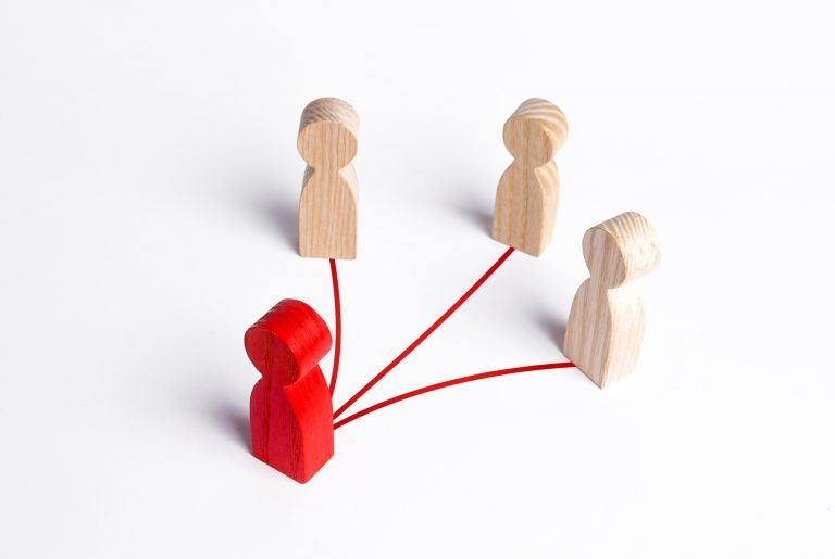 3 wooden figures with lines to a red figure