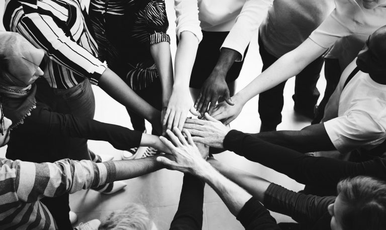 Black and white picture of many hands in a circle