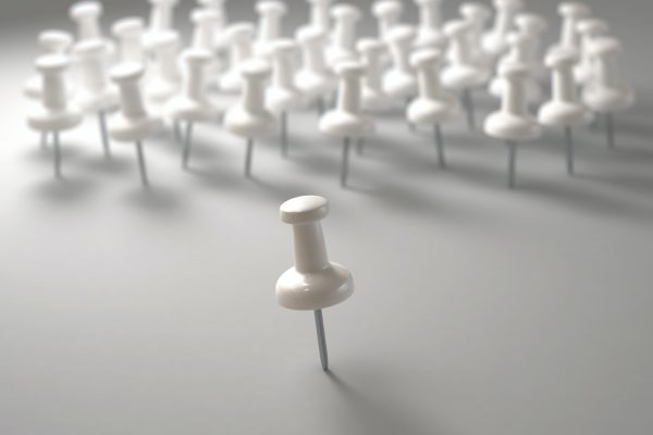 Group of white pins with a single pin in front