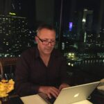 Picture of Riad Beladi at his laptop at a desk