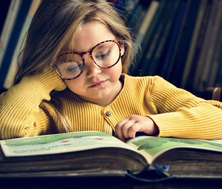 Young girl in glasses reading a story