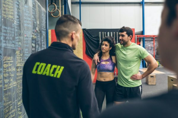 2 people standing in front of a gym coach