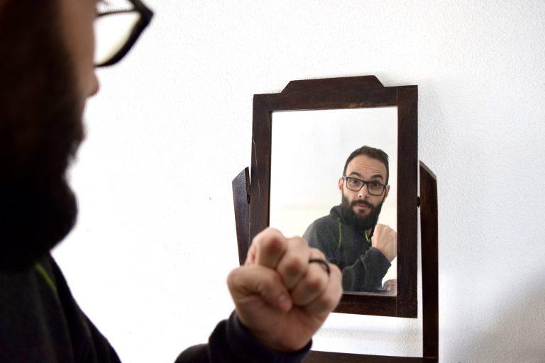 Man looking in the mirror cheering himself on