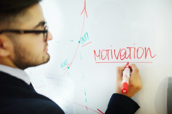 Man writing the word Motivation on a whiteboard