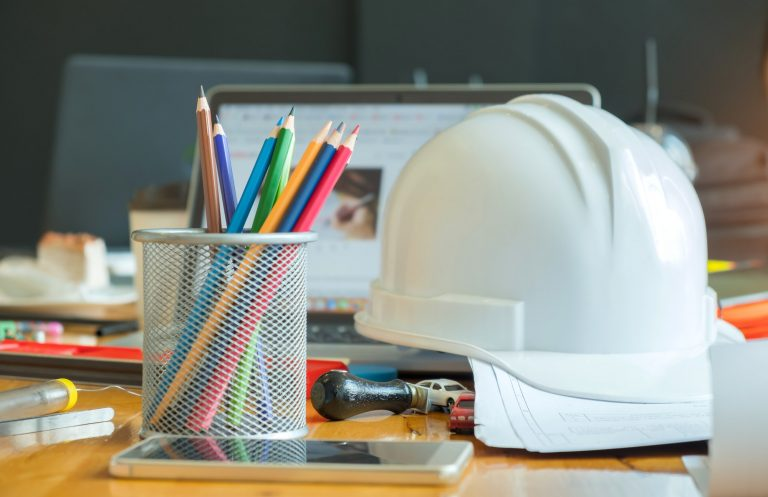 Multi colored pencils in box with safety helmet