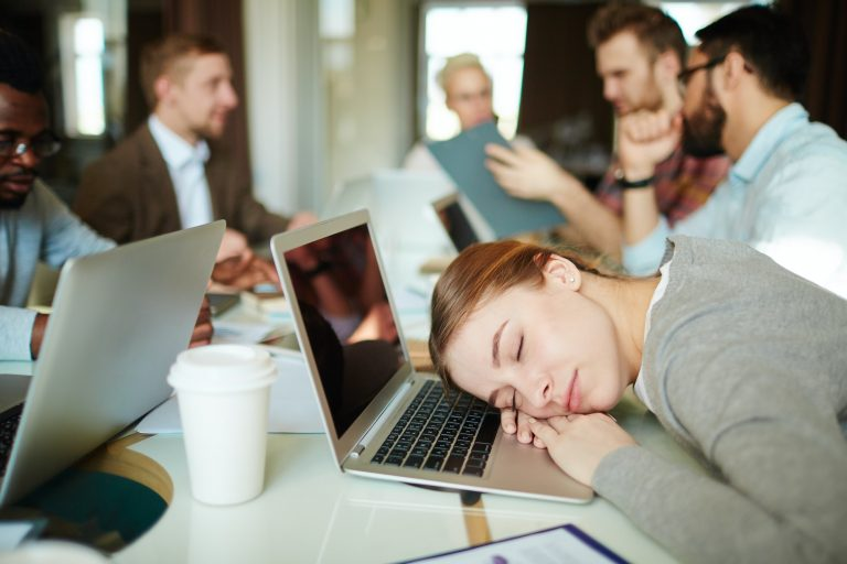 Woman asleep on laptop at a meeting